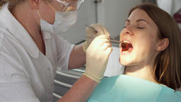 Dentist treating teeth to woman patient in clinic. Female professional doctor at Footage