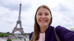 Woman near Eiffel Tower using mobile talking via messenger app. Smiling tourist Footage