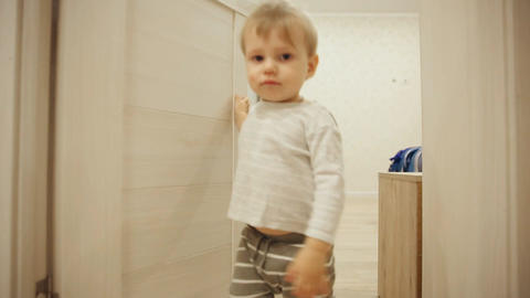 Little boy in pajamas while at home playing hide and seek with the door. Opens Footage