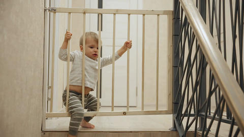 A little boy is sitting at home in front of the stairs behind the bars which Footage