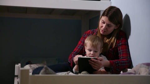 Close-up shot of son and mother in bed playing game on touch pad. Bedtime Footage