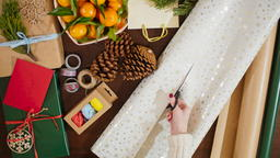 4K Top View of Female Hands Cutting Wrapping Paper for Box with Christmas Gift Photo