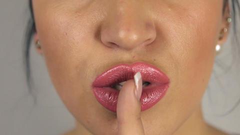 Brunette girl puts finger to her mouth, urging silent Footage
