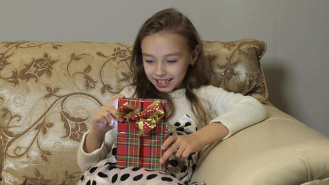 Cute little girl opens a gift box, surprise and joy. HD Footage