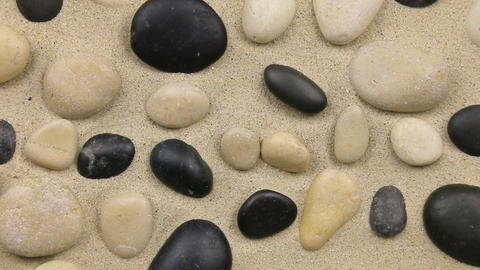 Approximation of black and white stones on the sand Footage