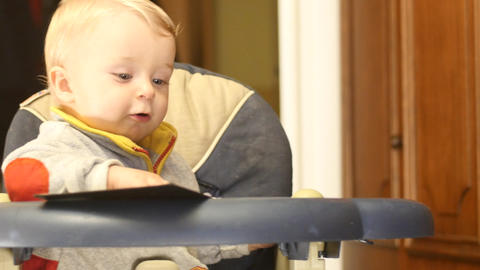 cute 9-10 months old baby boy turn pages of book Footage