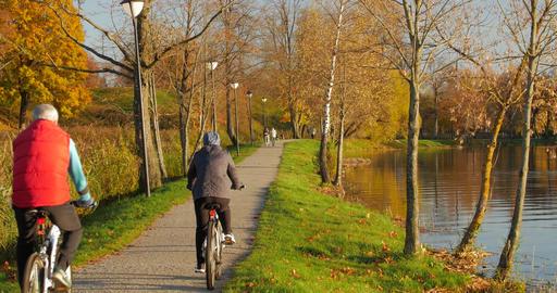 Lady and man bike together at lake shore Image