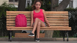Female College Student Relaxing On Park Bench Live Action