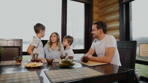 Family of four having Breakfast in his kitchen with large Windows. People are Footage