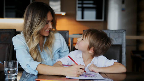 Beautiful mom helps her son to paint with colored pencils image. Helping to Footage