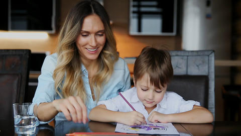 Beautiful mom helps her son to paint with colored pencils... Stock Video Footage