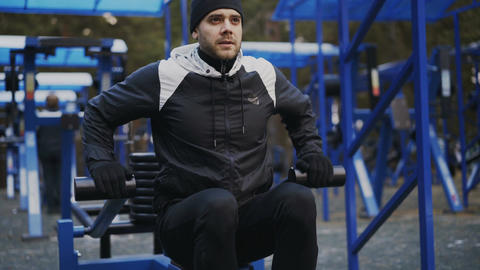 Handsome athlete man doing exercise at outdoor gym in winter park Footage