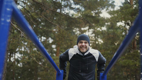 Young athlete man doing push-ups exercise on bars in winter park outdoors Footage