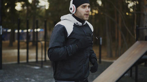 Attractive man in headphones doing warm-up exercise preparing for jogging while Footage