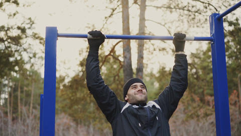 Young athletic man doing pull-up exercise in winter park outdoors Footage