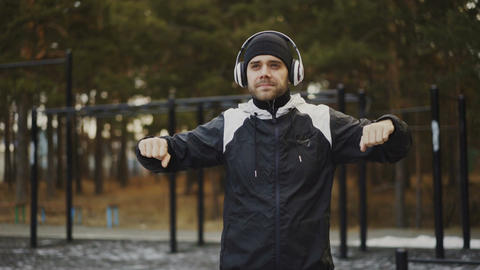 Handsome man in headphones doing warm-up exercise while listening music in Footage