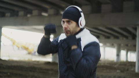 Stedicam shot of sportive man boxer in headphones doing boxing exercise in urban Live Action