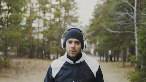 Tilt down shot of attractive runner man in headphones jogging while listening Footage