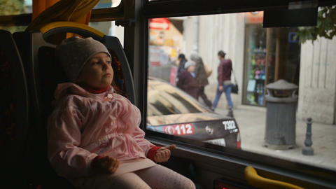 Little Blonde Girl in a pink jacket, Kid is Sitting in a Bus Cabin. Sitting on Filmmaterial