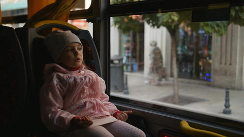 Little Blonde Girl in a pink jacket, Kid is Sitting in a Bus Cabin. Sitting on Footage