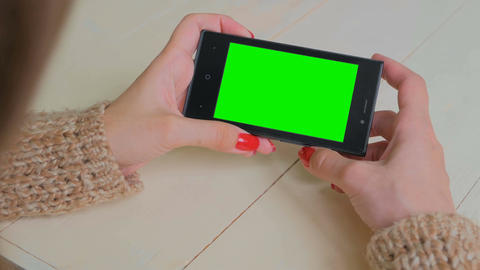 Woman looking at smartphone with green screen Archivo