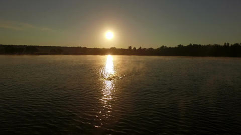 Aerial shot in slow motion of swimmer at sunset Live Action