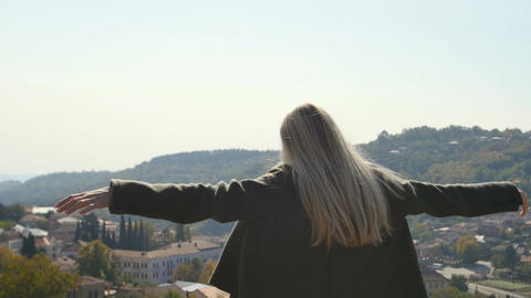 Young woman standing raised raising up hands looking at village and peaks Footage