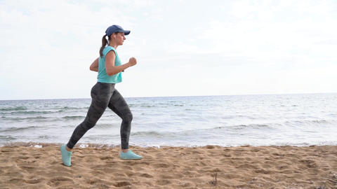 Athletic woman running along the beach. Video at different speeds - quick Footage