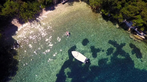 Aerial shot of a bay with boat and people floating on Lefkas, Greece Footage
