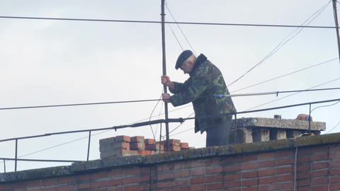 Man sets on a rooftop TV antenna Archivo