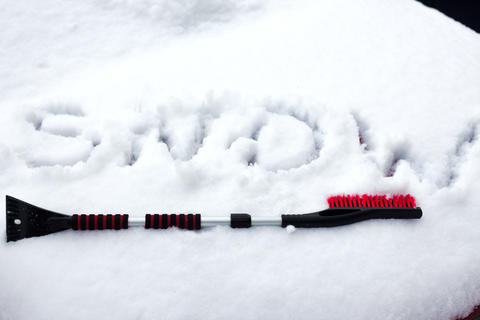 Closeup photo of black brush lying on car covered in snow Photo