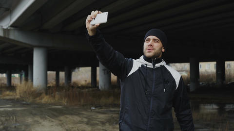 Happy sportive man taking selfie portrait with smartphone after training in Live Action