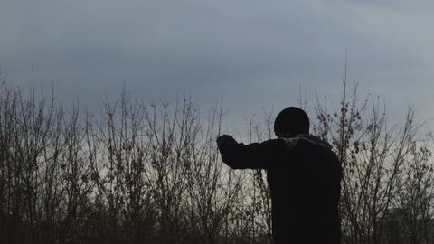 Slowmotion silhouette of sportive man boxer doing boxing exercise outdoors in Live Action