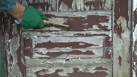 Scraping old brown paint from wooden door with scraper Footage
