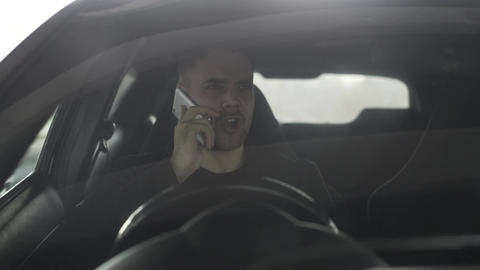 Upset angry businessman talking phone while sitting inside car outdoors Footage