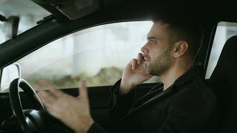 Stressed man swearing and talking phone while sitting inside car outdoors Footage
