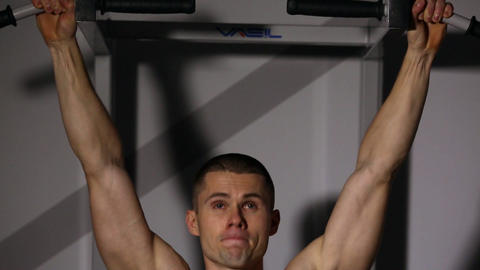 a man with a naked torso sit-UPS with leg raises on the horizontal bar in the Footage