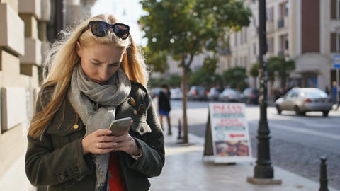 Portrait of young woman using phone, outdoors. Serious beautiful young woman Footage