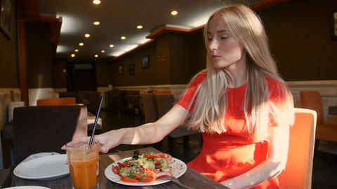 Woman in red dress eating fresh salad in a cafe Footage