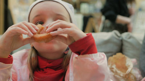 Little girl eats delicious donuts in the cafe Footage