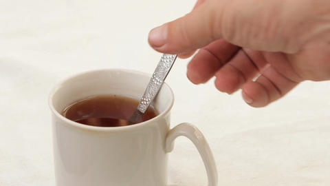 Pour into a cup of tea sugar with a teaspoon ビデオ