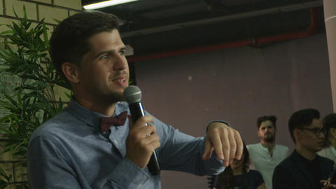 Side View Young Man with Bow Tie Speaks to Audience Footage