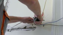 Electrician is installing electrical outlet box Live Action