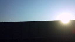 Beautiful sun over the fence in the road Footage