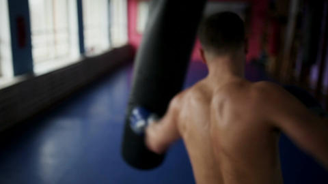 Rear view of male boxer makes punches for bag Boxing gloves at the gym Footage
