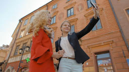 Two Tourist Girls are Making Photo Selfie with the Mobile Phone in the Old Town Footage