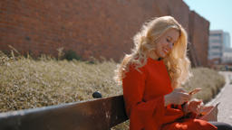 Beautiful Blonde Woman Sitting On a Bench And Using her Mobile Smart Phone App Footage