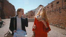 Two Women Tourists are Smiling and Talking while Walking in Street with Map Footage