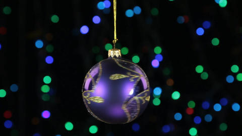 Close-up, the rotation of a lilac Christmas ball hanged on a golden rope Footage