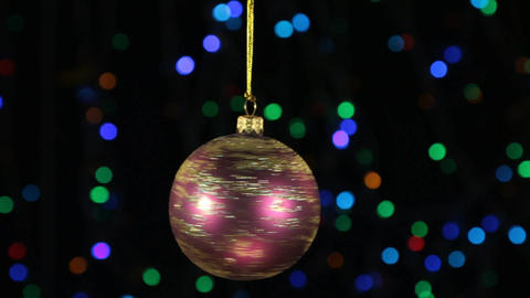 Close-up, the rotation of a red Christmas ball hanged on a golden rope Footage